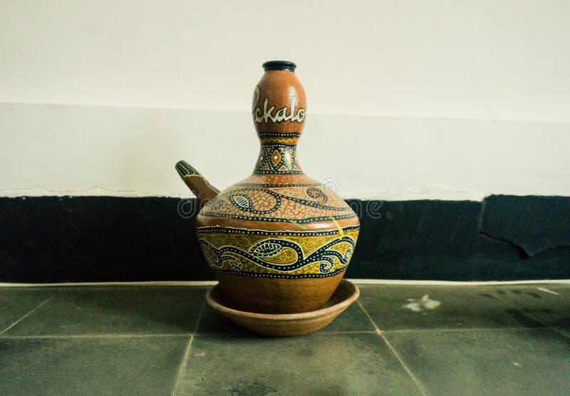 Kendi als eine von den traditionellen Tonwaren gemacht vom Lehm mit dem einzigartigen Motiv angezeigt im Batik-Museum Foto eingel stockfotos