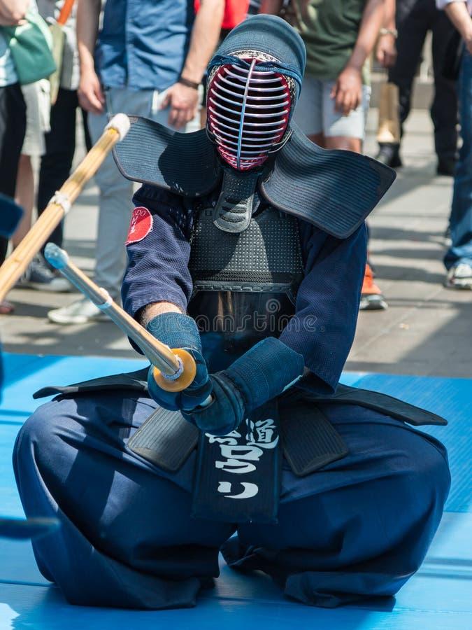 Kendo Warrior auf seinen Knien kämpfend in der traditionellen Kleidung und in B stockbild