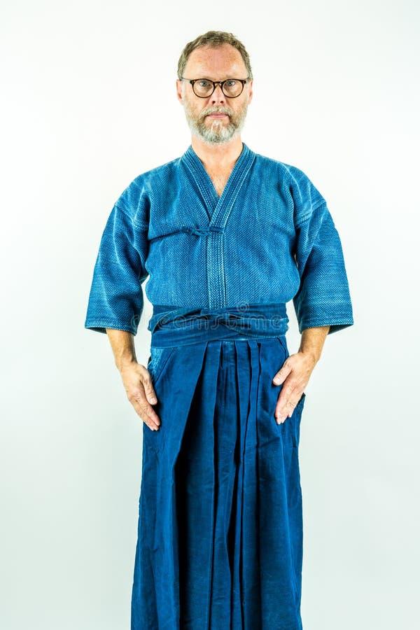 Kendoka - hombre en ropa, hakama y chaqueta del kendo Estudio tirado en el fondo blanco imagenes de archivo
