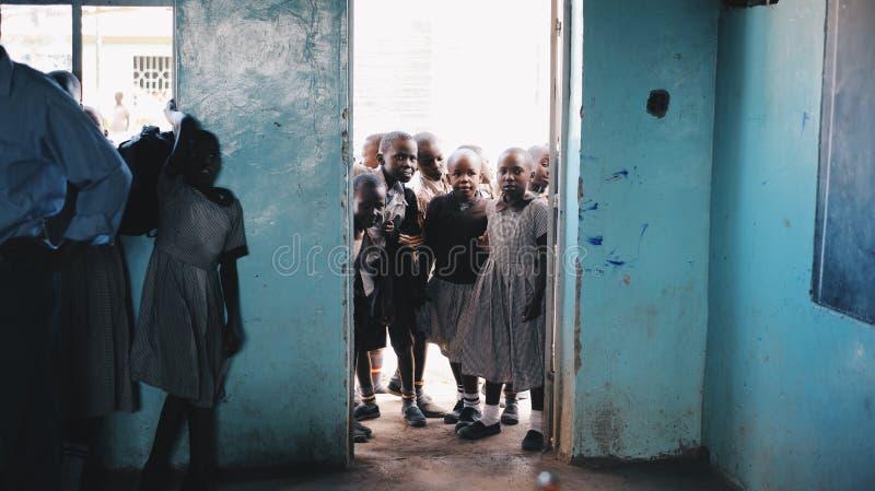 KENIA, KISUMU - 20 DE MAYO DE 2017: El grupo de niños en uniforme entra en la clase y se prepara para la lección en la escuela en foto de archivo