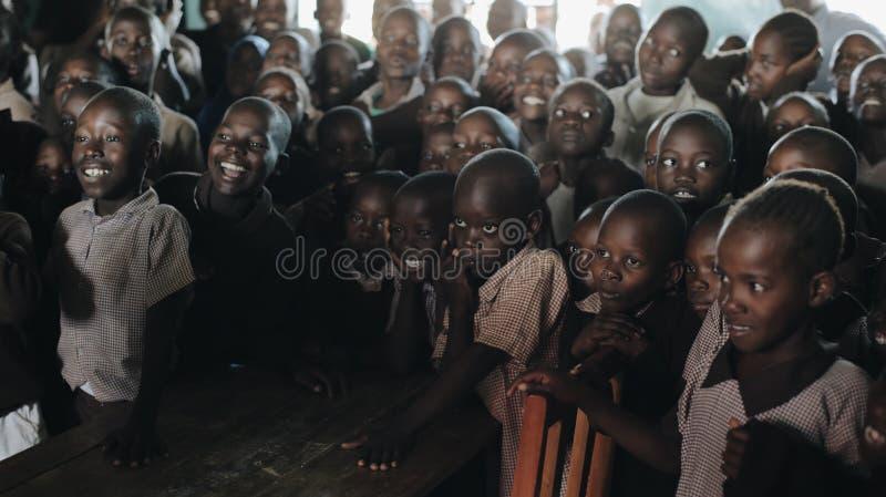 KENIA, KISUMU - 20 DE MAYO DE 2017: Grupo de niños africanos en risa uniforme y sonrisa junto en la lección en la escuela adentro fotografía de archivo