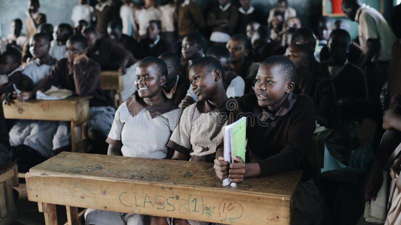 KENIA, KISUMU - 20 DE MAYO DE 2017: Grupo de niños africanos felices que se sientan en sala de clase y que sonríen, riendo junto foto de archivo libre de regalías