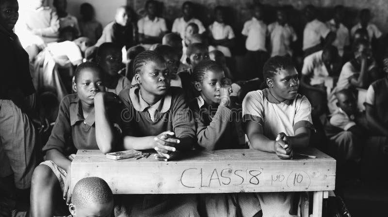 KENIA, KISUMU - 20. MAI 2017: Gruppe afrikanische Kinder in der Uniform, die im Klassenzimmer sitzt und, lächelnd gerade schaut lizenzfreie stockfotos