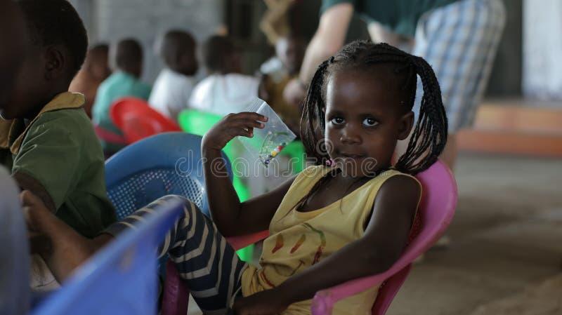 KENIA, KISUMU - 23 MEI, 2017: Portret van gelukkige Afrikaanse meisjeszitting binnen met groep kinderen en het dansen, het glimla royalty-vrije stock foto's