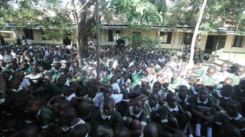 KENJA KISUMU, MAJ, - 23, 2017: Duży tłum Afrykańscy dzieci w jednolitym obsiadaniu na zmielonej outside pobliskiej szkole fotografia stock