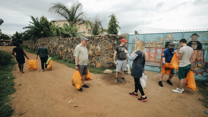 KENJA KISUMU, MAJ, - 20, 2017: Grupa Kaukascy ludzie z pakunkami Wolontariuszi podróżowali Afryka pomagać zdjęcie stock