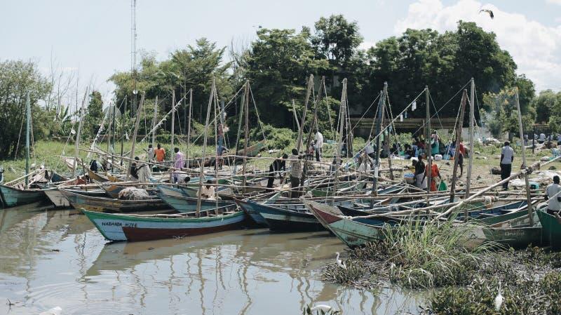 KENJA KISUMU, MAJ, - 20, 2017: Wiele statki blisko brzeg rzeka w Afryka Ludzie chodzi na plaży, port dla zdjęcia royalty free