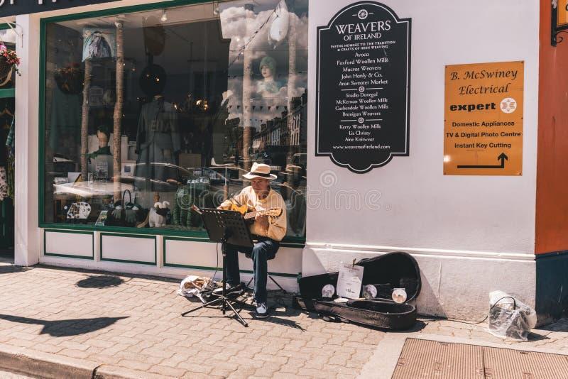 Kenmare, Irland - Kleinstadt im Süden der Grafschaft Kerry, Irland: Mann, der in den Straßen busking ist stockbild
