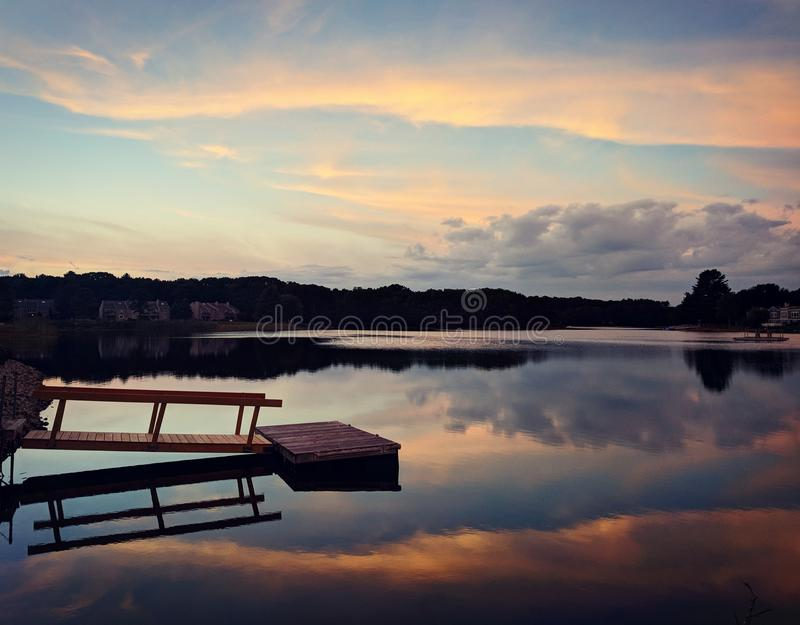 Sunset dock on lake in maine stock photo