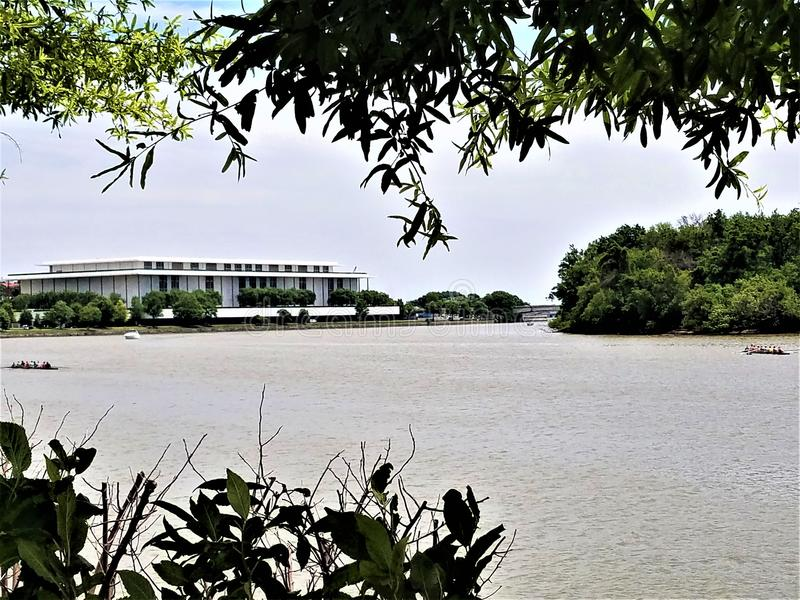 Kennedy Center on the Potomac with Crew Teams. The Kennedy Center viewed from the Boardwalk of the Washington Harbor overlooking the Potomac River at the stock images