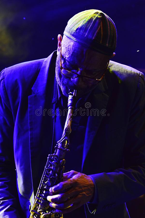 Kenny Garrett plays alto saxophone during summer jazz festival OpenJazzFest Zelena Voda, Slovakia, 30th of July 2017. There are some flies and midges behind stock image