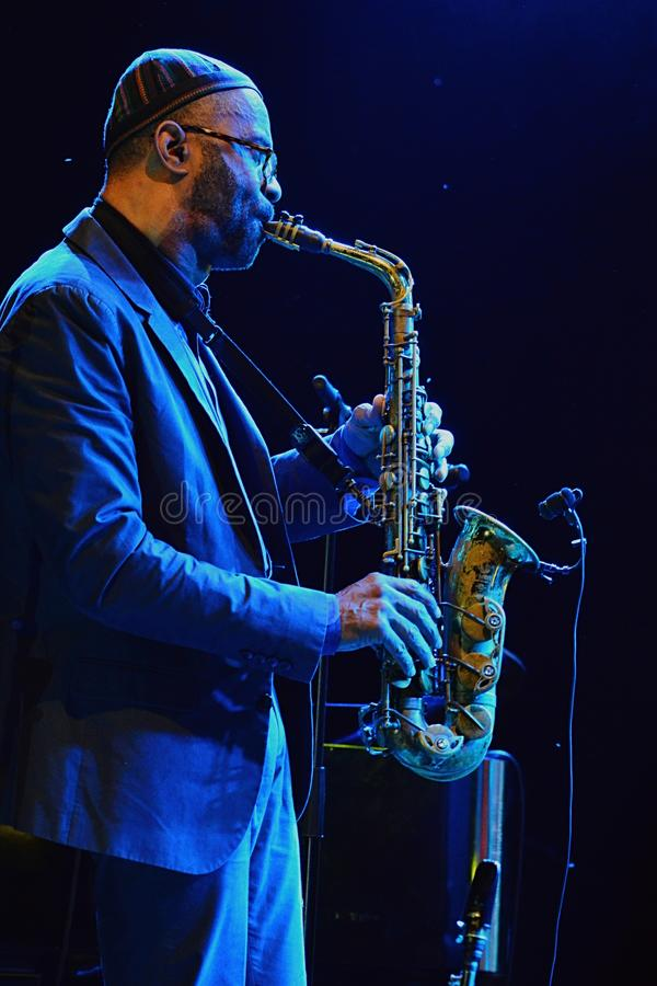 Kenny Garrett plays alto saxophone during summer jazz festival OpenJazzFest Zelena Voda, Slovakia, 30th of July 2017. There are some flies and midges behind royalty free stock images