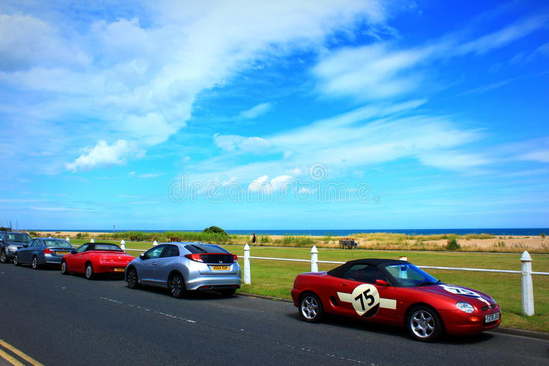 Kent coastal road nice cars England. Beautiful sports and family bright cars parked at the Beach Street against nice blue sky with cirrus wispy clouds on lovely stock images