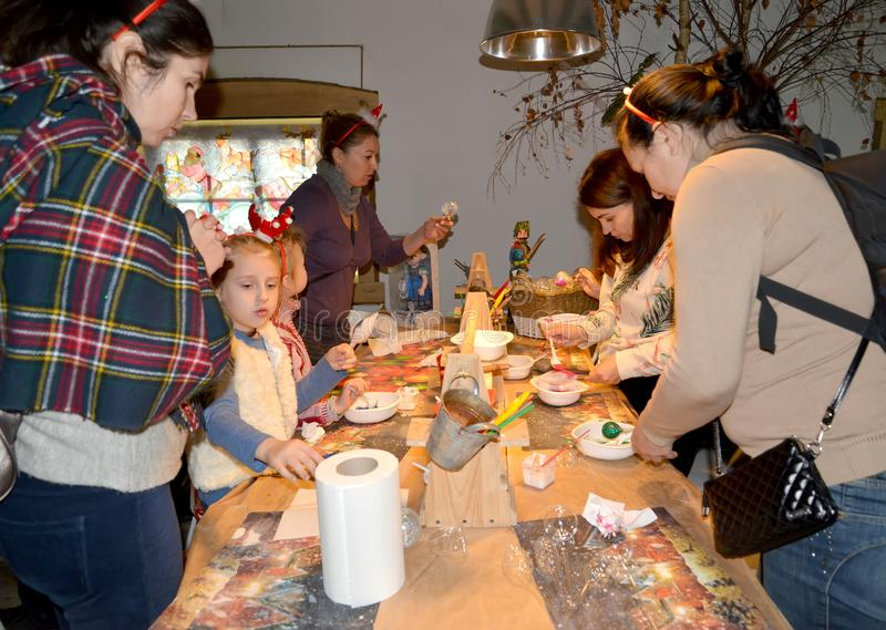 KENTSHIN, POLAND. Children and adults together at a master class on making Christmas toys royalty free stock photo