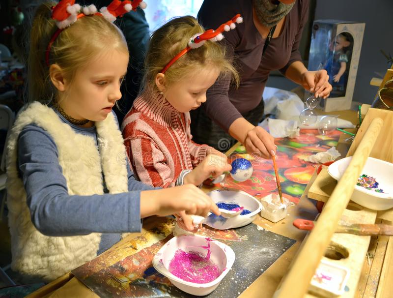 KENTSHIN, POLAND. Children sprinkle Christmas toys with glitter. Children `s master class in the workshop stock image