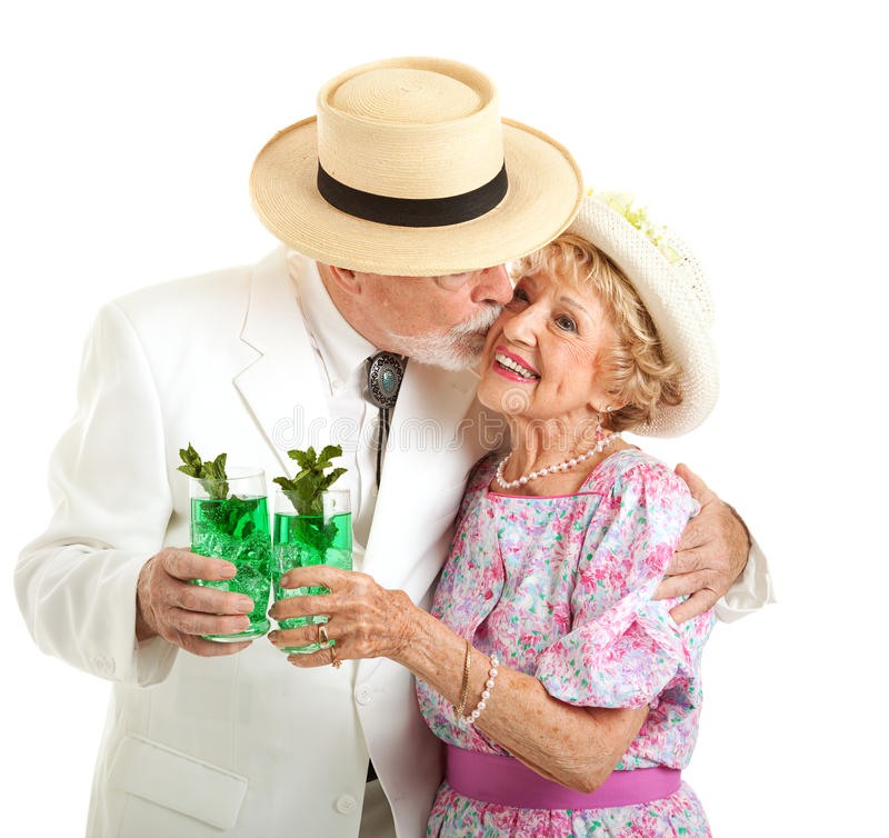 Kentucky Derby - Southern Seniors Kiss. Southern senior couple dressed for the Kentucky Derby, holding mint juleps and kissing stock image
