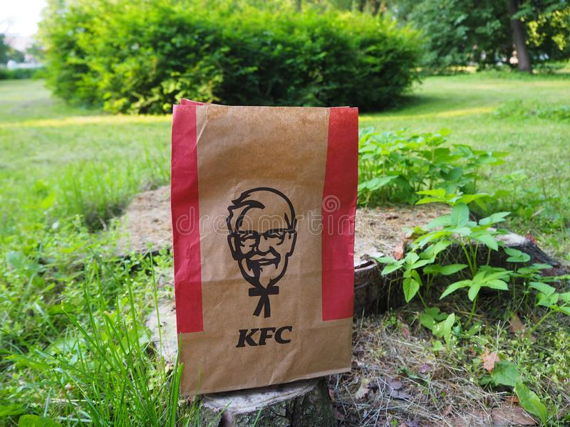 Kentucky Fried Chicken paper bag on a tree stump in the park. stock images