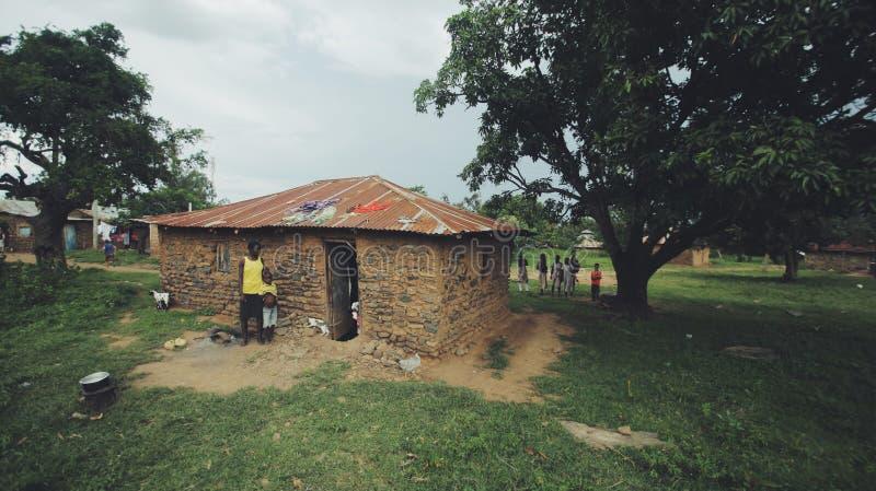 KENYA, KISUMU - 20 DE MAIO DE 2017: A família africana pobre está perto de sua casa Mamã e crianças em uma vila em África imagem de stock royalty free