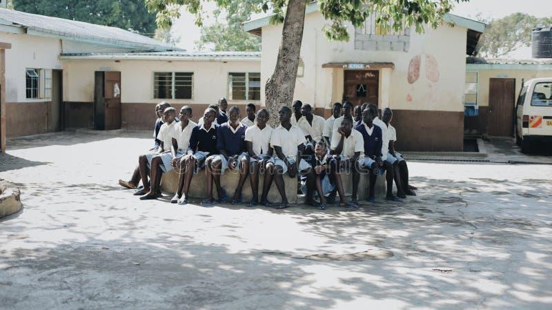 KENYA, KISUMU - 20 DE MAIO DE 2017: Grupo de crianças africanas que sentam-se no banco Meninos e meninas que passam o tempo perto fotografia de stock