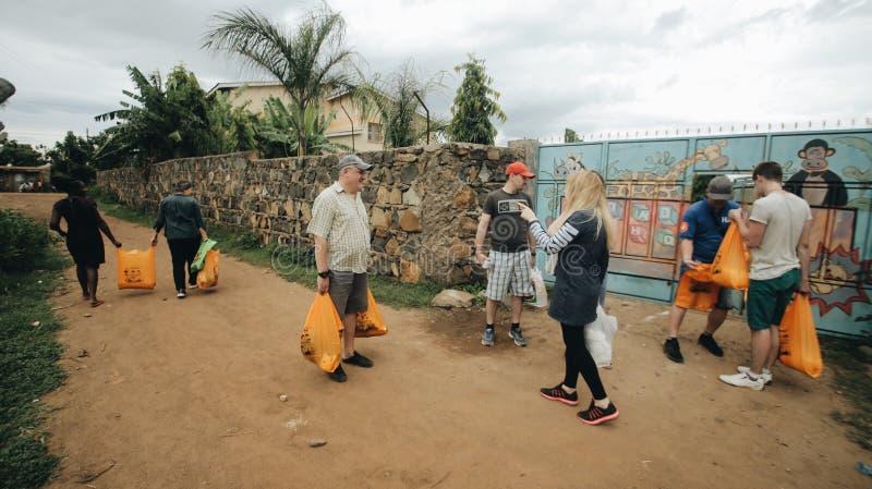 KENYA, KISUMU - 20 DE MAIO DE 2017: Grupo de povos caucasianos com pacotes Os voluntários viajaram a África para ajudar foto de stock