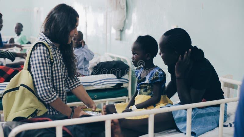 KENYA, KISUMU - 20 DE MAIO DE 2017: Grupo de povos caucasianos que guardam pouco childe africano nas mãos Voluntários no hospital imagens de stock