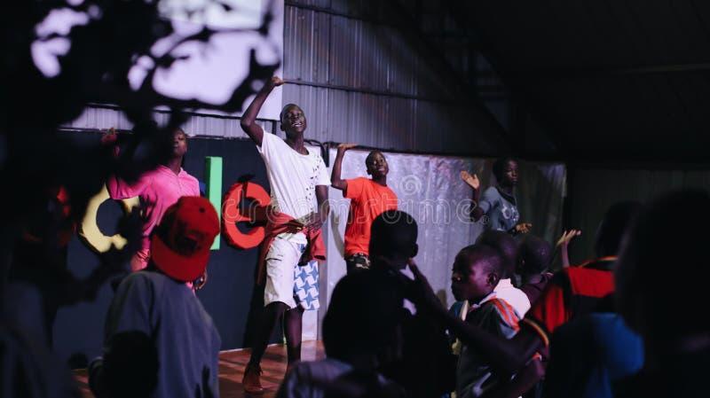 KENYA KISUMU - MAJ 20, 2017: Den stora gruppen av afrikanska barn som inom tillsammans dansar, lyssnar musik och att sjunga royaltyfria bilder