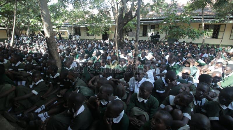 KENYA KISUMU - MAJ 23, 2017: Stor folkmassa av afrikanska barn i likformign som sitter på en jordyttersida nära skola royaltyfri foto