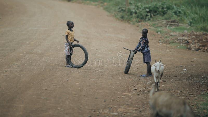 KENYA KISUMU - MAJ 20, 2017: Två afrikanska pojkar som spelar med gummihjul på vägen Ungar som har gyckel tillsammans royaltyfria foton