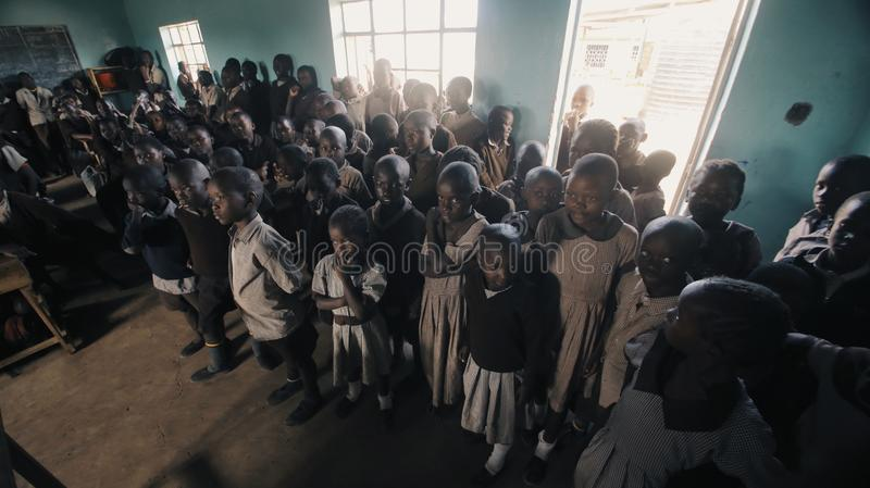 KENYA, KISUMU - MAY 20, 2017: Crowd of african children standing in big classroom. Boys and girls from poor african. Village. Bald kids waiting for lesson in royalty free stock photography