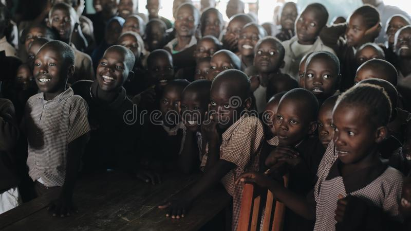 KENYA, KISUMU - MAY 20, 2017: Group of African children in uniform laugh and smile together at lesson at school in stock photography