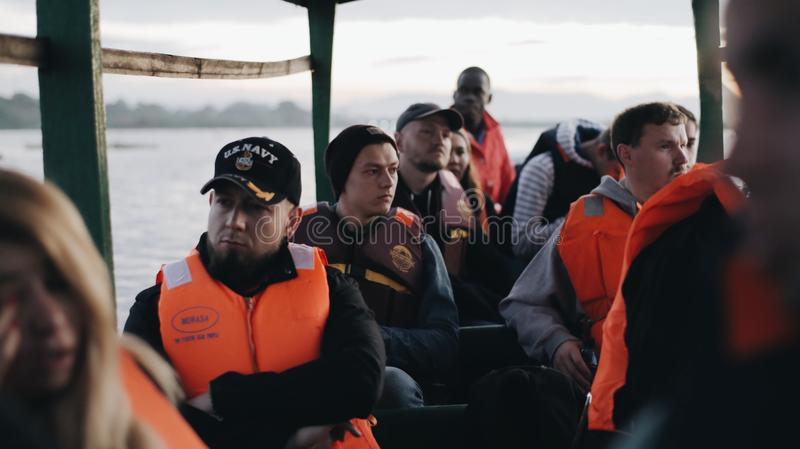KENYA, KISUMU - MAY 20, 2017: Group of Caucasian people and African sailor sitting in boat. Tourists explore Africa by stock photo