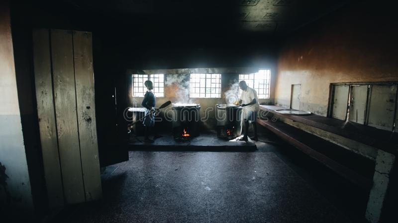 KENYA, KISUMU - MAY 20, 2017: Smoking pots in the kitchen near the window. Food is cooked in big boilers with cap. Poor hut in Africa royalty free stock photo