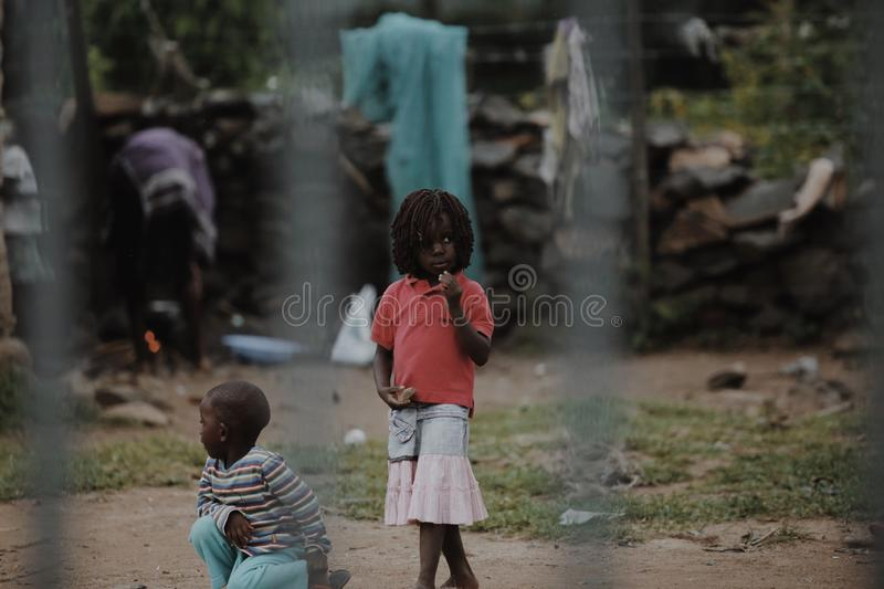 KENYA, KISUMU - MAY 20, 2017: View through the fence. Group of african people spending time outside. Little girl having royalty free stock photography