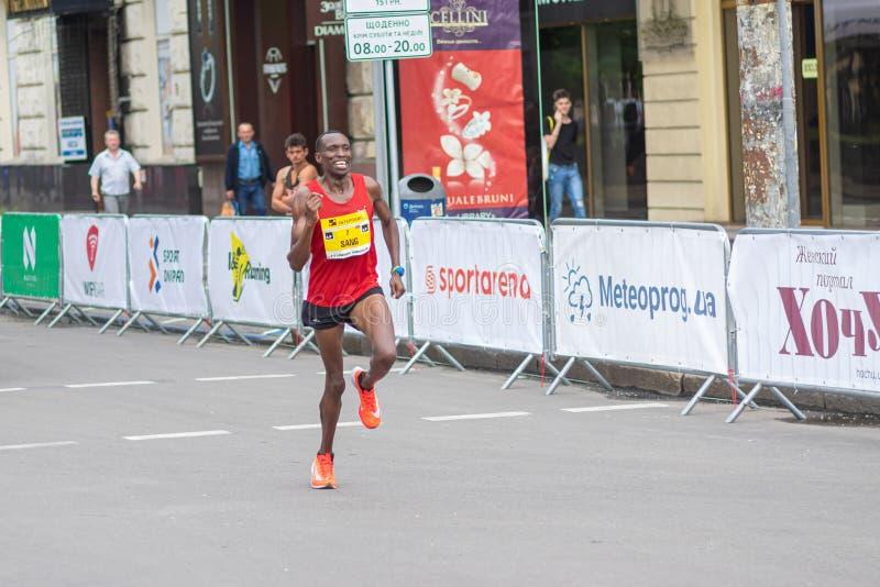 Kenyan Sieger, der auf einer Allee Dmytra Yavornitskoho während des Halbmarathonrennens Interipe Dnipro läuft lizenzfreie stockfotos