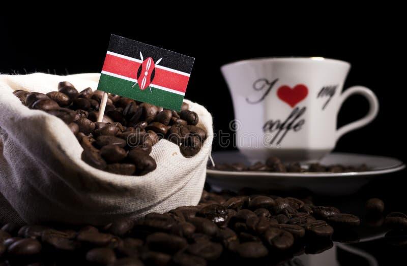 Kenyanflagge in einer Tasche mit den Kaffeebohnen lokalisiert auf Schwarzem lizenzfreies stockbild