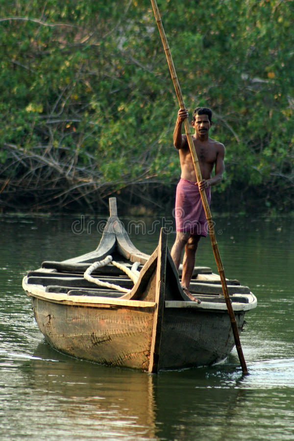 Kerala boatman. Boatman on a large wooden boat using long bamboo stick to move it in one of the narrow water channels in the Kerala backwaters, Kerala, India stock photography