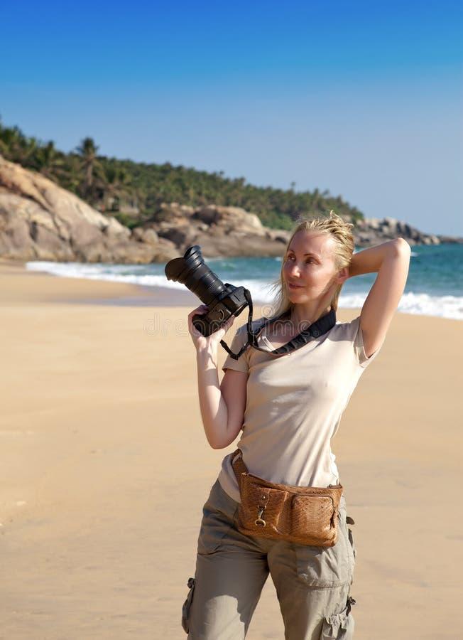 Kerala A mulher bonita nova com a câmera em uma praia fotos de stock