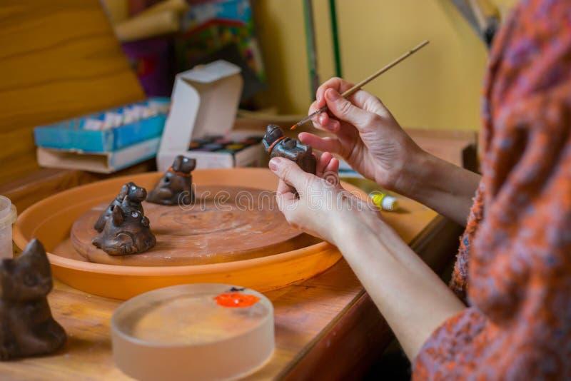 Keramiker för yrkesmässig kvinna som målar den keramiska souvenirencentmyntvisslingen i krukmakeri royaltyfria bilder