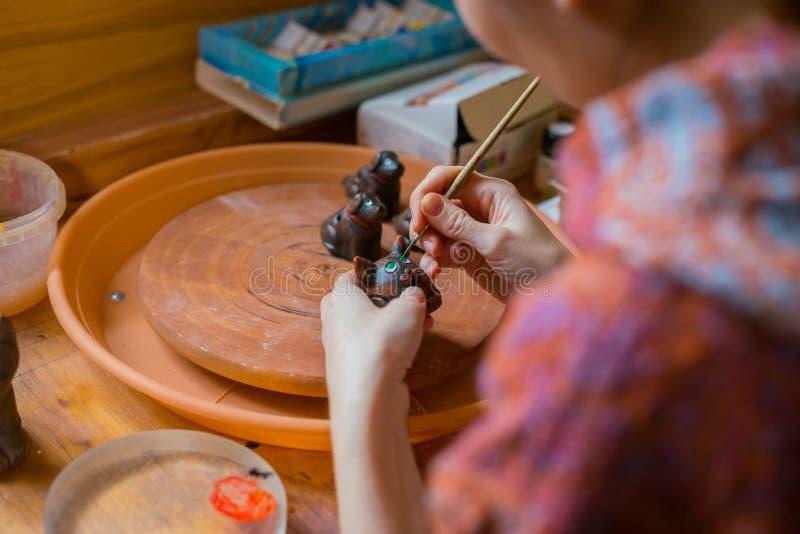 Keramiker för yrkesmässig kvinna som målar den keramiska souvenirencentmyntvisslingen i krukmakeri royaltyfri bild