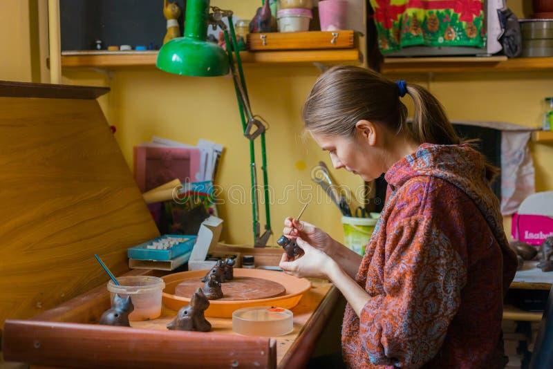 Keramiker f?r yrkesm?ssig kvinna som m?lar den keramiska souvenirencentmyntvisslingen i krukmakeri arkivbilder