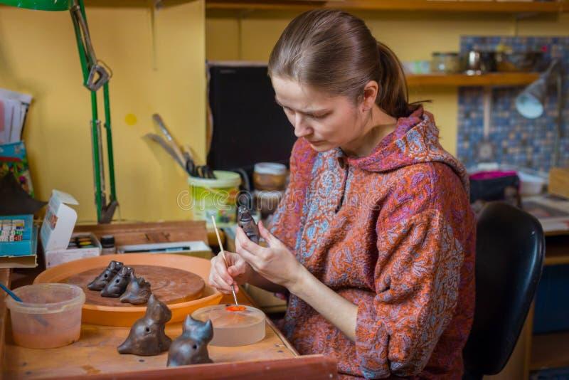 Keramiker f?r yrkesm?ssig kvinna som m?lar den keramiska souvenirencentmyntvisslingen i krukmakeri royaltyfri foto