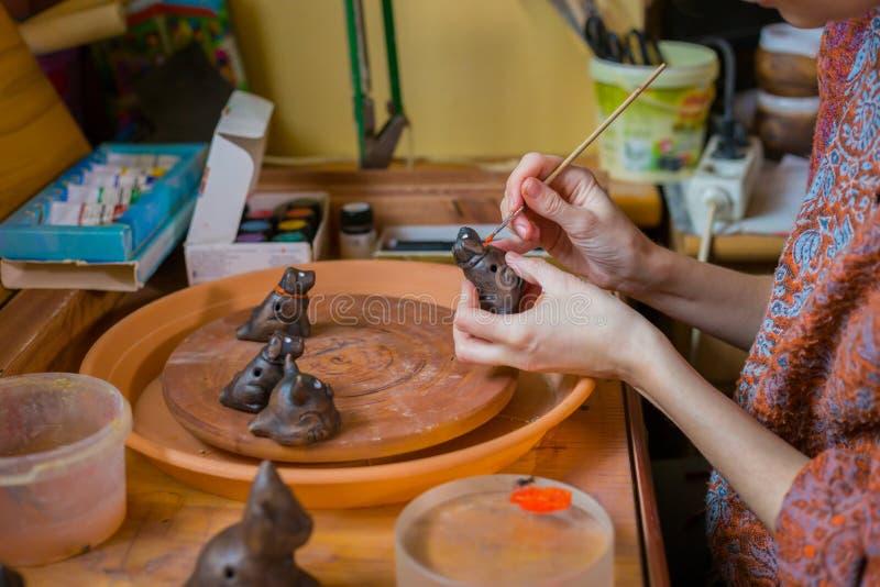 Keramiker f?r yrkesm?ssig kvinna som m?lar den keramiska souvenirencentmyntvisslingen i krukmakeri fotografering för bildbyråer