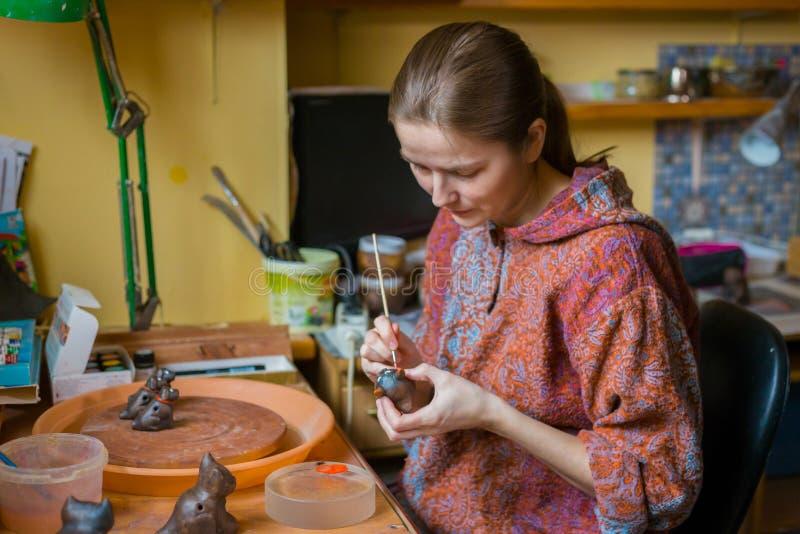 Keramiker f?r yrkesm?ssig kvinna som m?lar den keramiska souvenirencentmyntvisslingen i krukmakeri arkivfoton