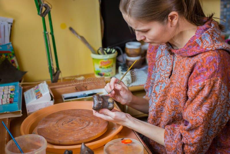 Keramiker f?r yrkesm?ssig kvinna som m?lar den keramiska souvenirencentmyntvisslingen i krukmakeri royaltyfria foton