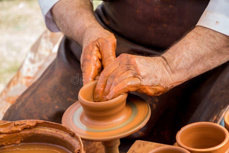 Keramiker` s räcker att forma upp leran arkivfoto