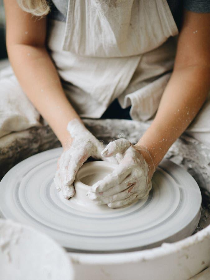 Keramiker som arbetar med lera på hjulet arkivbilder
