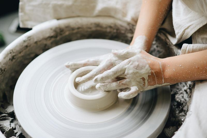 Keramiker som arbetar med lera på hjulet arkivfoto