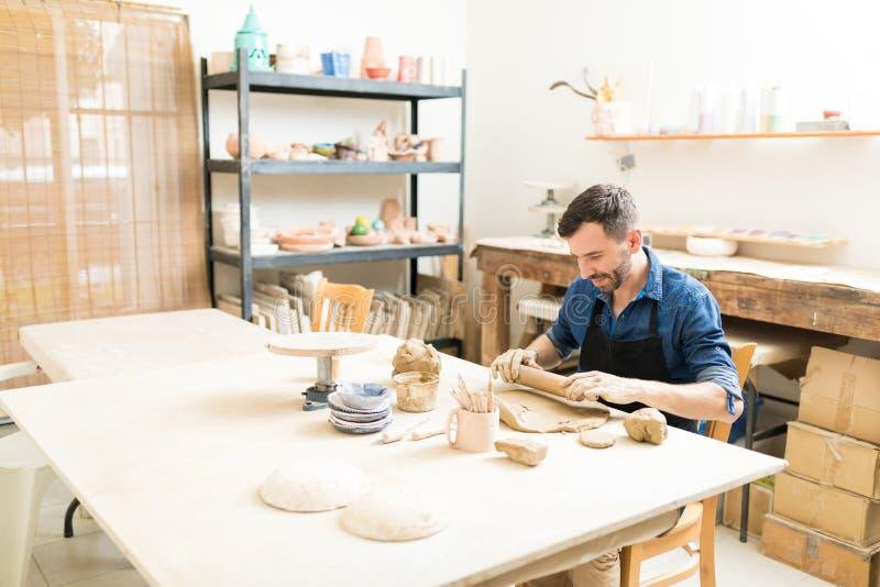Keramiker som gjuter det Clay With Rolling Pin In krukmakeriseminariet arkivfoton