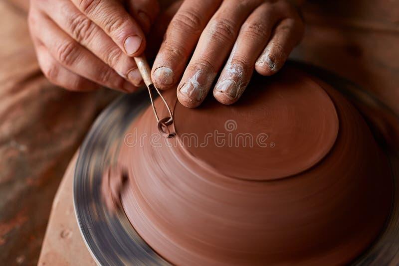 Keramikerförlage för vuxen man som modellerar leraplattan på hjulet för keramiker` s Den bästa sikten, closeup, räcker endast arkivfoton