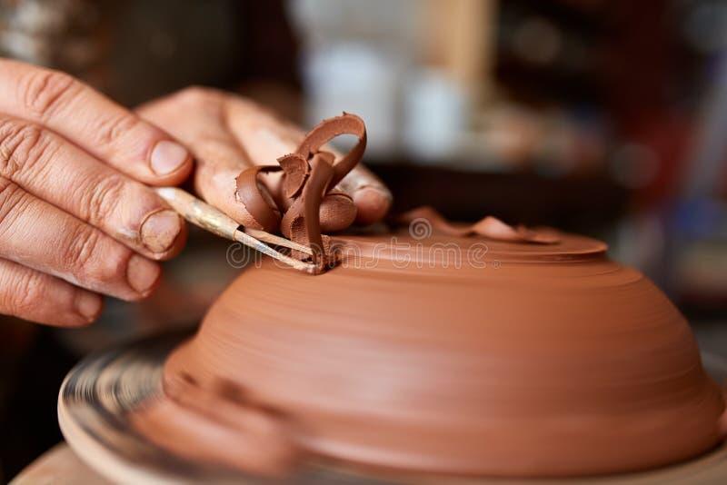 Keramikerförlage för vuxen man som modellerar leraplattan på hjulet för keramiker` s Den bästa sikten, closeup, räcker endast royaltyfria foton